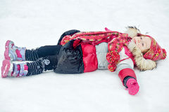 Little girl lies on snow with hands stretched to sides Stock Images