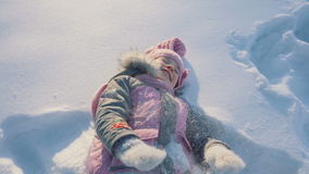 Little girl lies on snow stock video footage