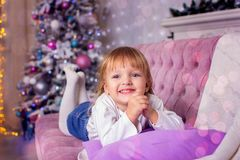 The little girl lies on a sofa against the background of a Christmas tree. In a photographic studio Stock Photography