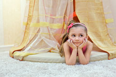 Little girl lies under baldachin Stock Photos
