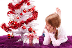 Little girl lies under the Christmas tree Royalty Free Stock Photo