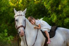 The little girl lies on a horse. The little girl lies on a white horse Stock Photography