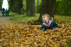 Little girl lies at yellow leaves. Small happy girl with two funny ponytails lies at the yellow leaves royalty free stock photos