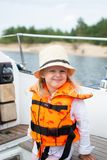 Little Girl in Life Vest Staying on the Sailboat, Yachting, Cloudy Sky. Travel stock photography