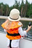 Little Girl in Life Vest Staying on the Sailboat, Yachting, Cloudy Sky. Travel stock photo