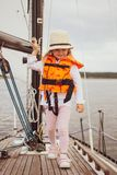 Little Girl in Life Vest Staying on the Sailboat, Yachting, Cloudy Sky. Travel royalty free stock image