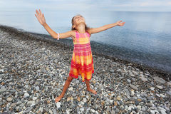 Little girl lifted hands upwards on stony beach Royalty Free Stock Image