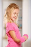 Little girl lifting a dumbbell royalty free stock photo