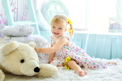 Little girl in light bedroom with big white teddy bear Stock Photos