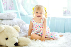 Little girl in light bedroom with big white teddy bear. Little smiling girl sitting on bed in light bedroom with big white teddy bear royalty free stock photo