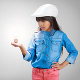 Little girl with a light bulb in hand Royalty Free Stock Photography