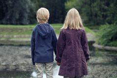 Little Girl with light hair And Boy In Blue Jacket Standing Back On Bank Of River And looking on the park stock photos