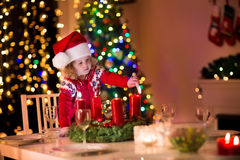 Little girl lighting candles at Christmas dinner Royalty Free Stock Images
