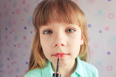 Little girl lipstick. The girl has painted eyelashes Stock Image