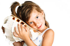 Little girl listening a huge seashell isolated Royalty Free Stock Image