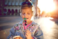 Little girl  listening  music  and eating  fruit lollipop,beauti Royalty Free Stock Photos