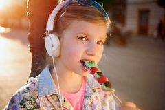 Little girl  listening  music  and eating  fruit lollipop,beauti Royalty Free Stock Images