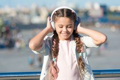Little girl listening music enjoy favorite song. Girl with headphones urban background. Positive influence of music. Child girl enjoying music modern earphones royalty free stock image