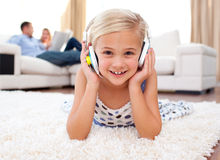 Little girl listening music lying on the floor Royalty Free Stock Photography