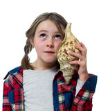 Little girl listening a shell Stock Photos