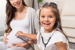 Girl listening to pregnant belly through stethoscope Royalty Free Stock Photos