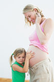Little girl listening to blonde mothers pregnant belly Royalty Free Stock Photo