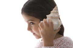 Little Girl Is Listening To A Large Sea Shell Royalty Free Stock Image
