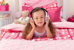 Little girl listening to music. And lying on bed Royalty Free Stock Images