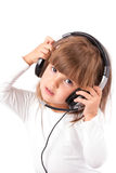 Little girl is listening to music. Little girl listens to music on headphones and singing royalty free stock image
