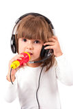 Little girl is listening to music. Little girl listens to music on headphones and singing Stock Photos
