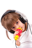 Little girl is listening to music. Little girl listens to music on headphones and singing stock photo
