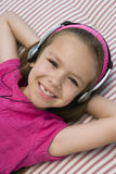 Little Girl Listening To Music. Portrait of a happy little girl listening to music while lying on mattress Royalty Free Stock Photography