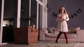 Little girl listening to music and dancing stock footage