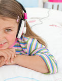 Little girl listening to music with headphones. Lying on her bed Royalty Free Stock Images