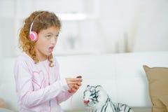 Little girl listening to music through headphones stock photo