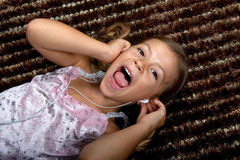 Little girl listening to music on headphones. Pretty little girl listening to music on headphones and singing out loud Stock Photo