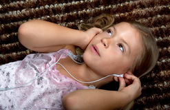 Little girl listening to music on headphones Stock Photo