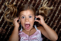 Little girl listening to music on headphones. Pretty little girl listening to music on headphones and screaming out loud Stock Photography