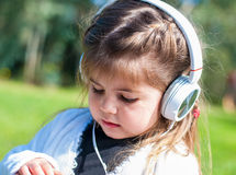 Little girl listening to music. Girl listening to music with headphones Royalty Free Stock Images