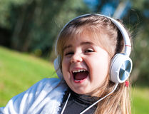 Little girl listening to music. Girl listening to music with headphones Royalty Free Stock Image