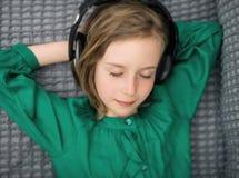 Little girl listening to the music. Little girl listening to the music in headphones Royalty Free Stock Image