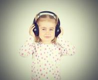 Little girl listening to music. On headphones Stock Photography
