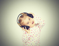 Little girl listening to music. On headphones Stock Image