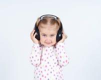 Little girl listening to music. On headphones Stock Images