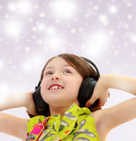Little girl listening to music headphones. Blue Christmas festive background with white snowflakes.Closeup portrait of little girl listening to music through Stock Photo