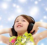Little girl listening to music headphones. Closeup portrait of little girl listening to music through big black headphones.Blue Christmas festive background Royalty Free Stock Images