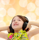 Little girl listening to music headphones. Closeup portrait of little girl listening to music through big black headphones.Brown festive, Christmas background Stock Photos