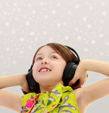 Little girl listening to music headphones. Closeup portrait of little girl listening to music through big black headphones.Gray background with round white Royalty Free Stock Photo