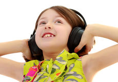 Little girl listening to music headphones. Royalty Free Stock Photography