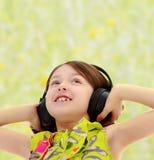 Little girl listening to music headphones. Closeup portrait of little girl listening to music through big black headphones.Summer white green blurred background Royalty Free Stock Photos
